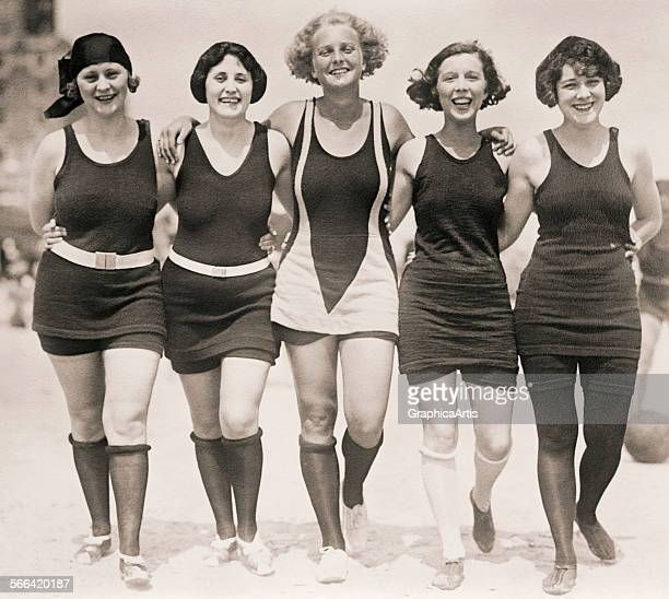 Five 1920s girlfriends pose arminarm on the beach in their wool bathing suits sepiatoned silver print circa 1920s