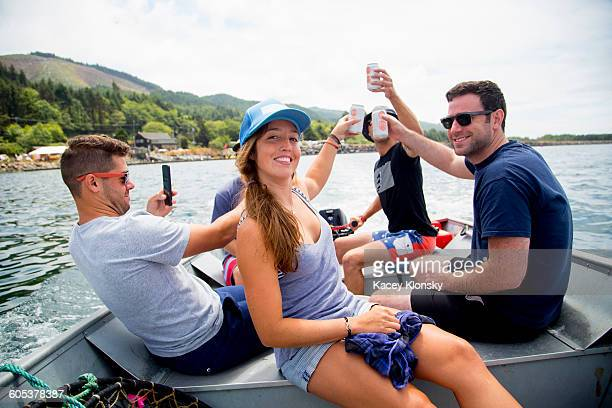 Five adult friends raising a beer can on fishing boat at Nehalem Bay, Oregon, USA