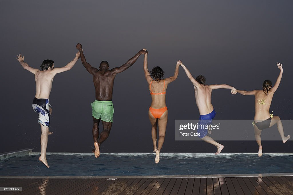 Five adults jumping into pool at night : Stock Photo