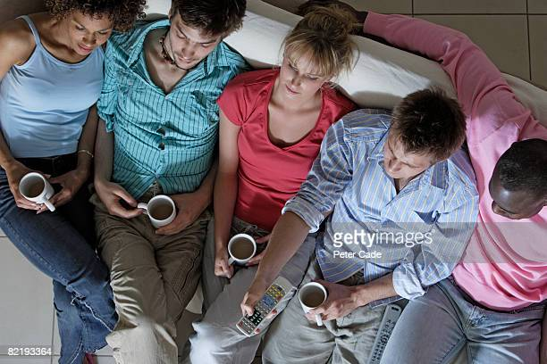 Five adults sat on sofa drinking and watching tv
