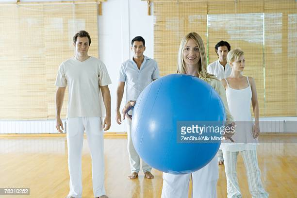 five adults standing in wellness center, woman in foreground holding fitness ball - man with big balls stock photos and pictures