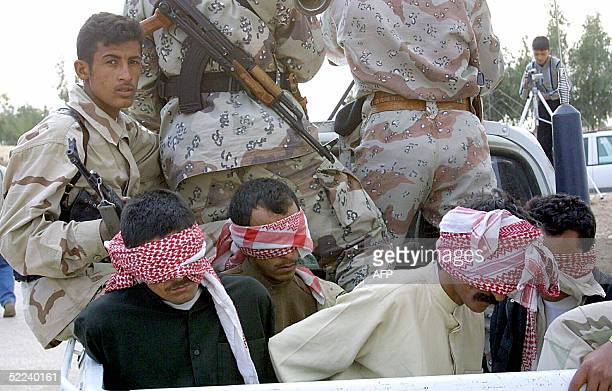Five alleged insurgents sit blindfolded in an Iraqi army truck in the holy city if Najaf 25 February 2005 Iraqi border police chief Major General...