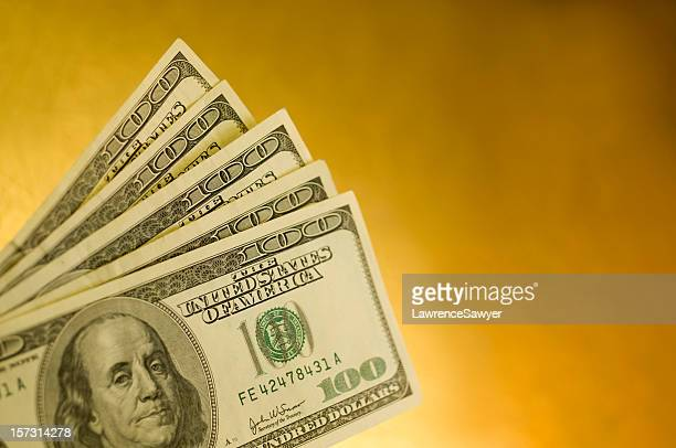 Five American one hundred dollar bills isolated on yellow