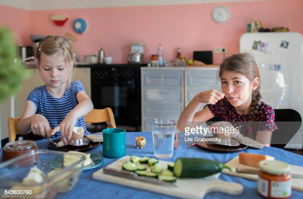 A five and a sevenyearold girl are having breakfast together and eat boiled eggs on August 07 2017 in Bonn Germany