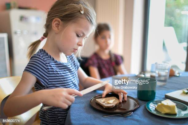 A five and a sevenyearold girl are having breakfast together One girl is spreading bread with butter on August 07 2017 in Bonn Germany