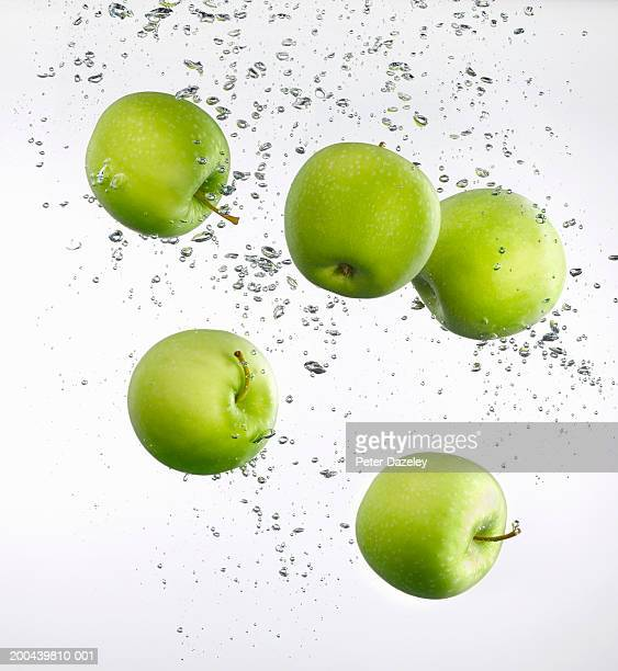 Five apples floating in water, close-up