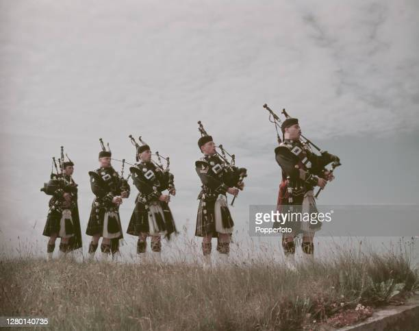 Five bagpipers in full highland military dress play great highland bagpipes in rehearsal ahead of performing at the Edinburgh Festival in Scotland in...