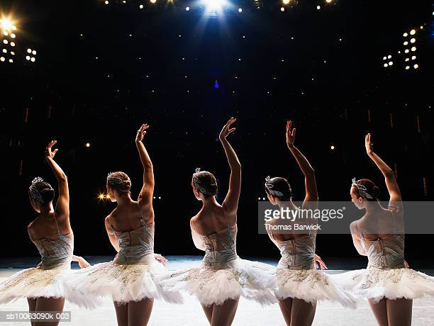 Five ballerinas dancing in line on stage, arms raised, rear view