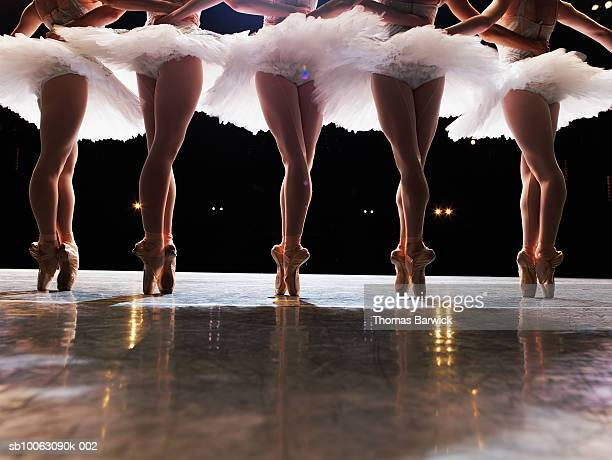 Five ballerinas en pointe on stage, arms around each other, rear, low section