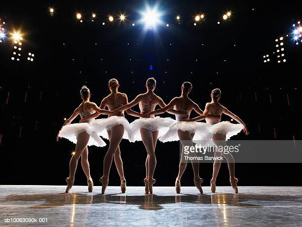 five ballerinas en pointe on stage, arms around each other, rear view - performing arts event stock pictures, royalty-free photos & images