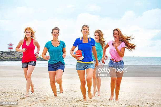 Five beautiful female beach volleyball friends posing for group photo