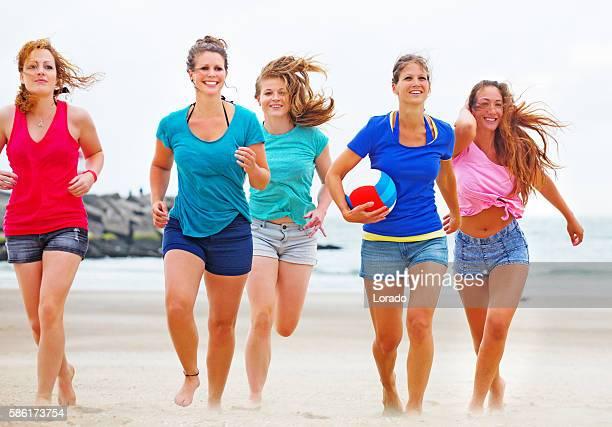 Five beautiful female friends having summer fun on sandy beach