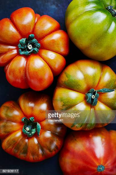 Five beef tomatos on black ground, elevated view