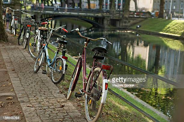 Five bicycles parked in a row next to a river