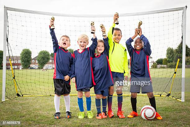 Five boys standing in football goal with trophies