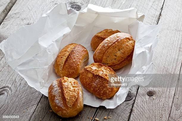 Five bread rolls on paper and grey wood