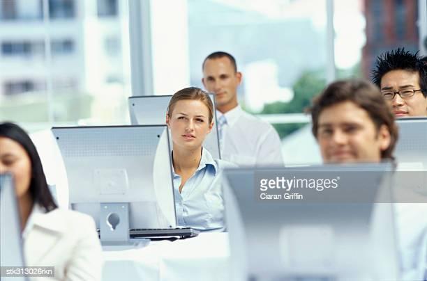 five business executives sitting at a seminar