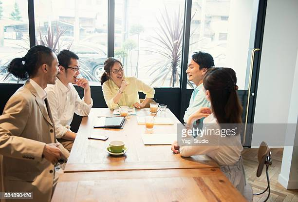 Five business people meeting in a cafe