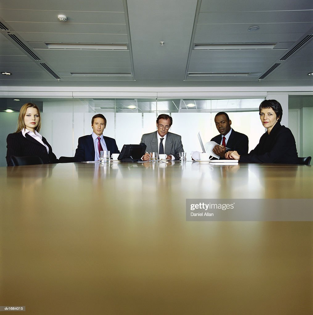 Five Business People Sitting at the far end of a Table in a Conference Room : Stock Photo