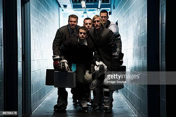 Five businessmen wearing ice hockey uniforms
