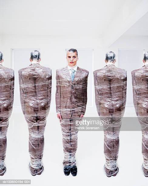 five businessmen wrapped in plastic wrap (digital composite) - man wrapped in plastic stock pictures, royalty-free photos & images