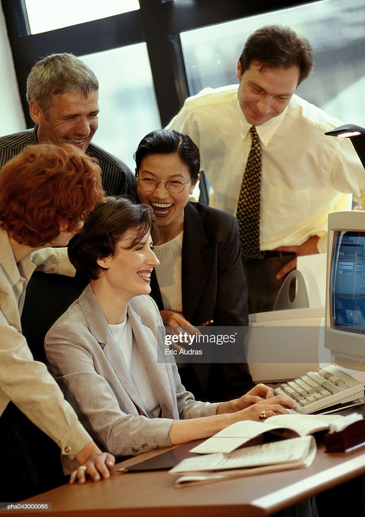 Five businesspeople gathered in front of desk : Stockfoto