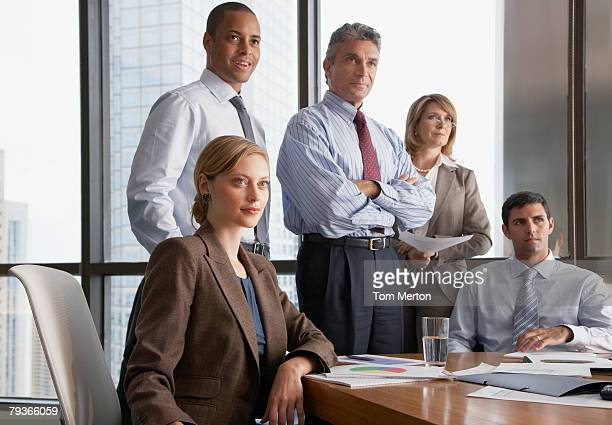 Five businesspeople in boardroom by large windows