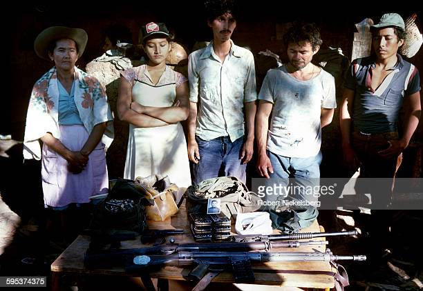 Five captured members of the governmentsponsored paramilitary National Democratic Organization stand behind a table of weapons following the Popular...