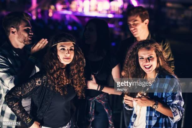 Five cheerful friends enjoying music at the summer rock festival.