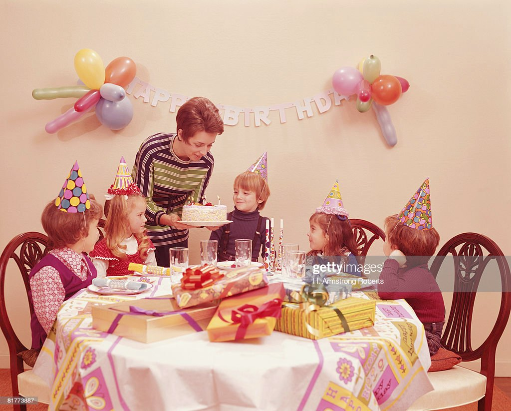 Five children at birthday party, mother serving birthday cake. (Photo by H. Armstrong Roberts/Retrofile/Getty Images) : Foto de stock