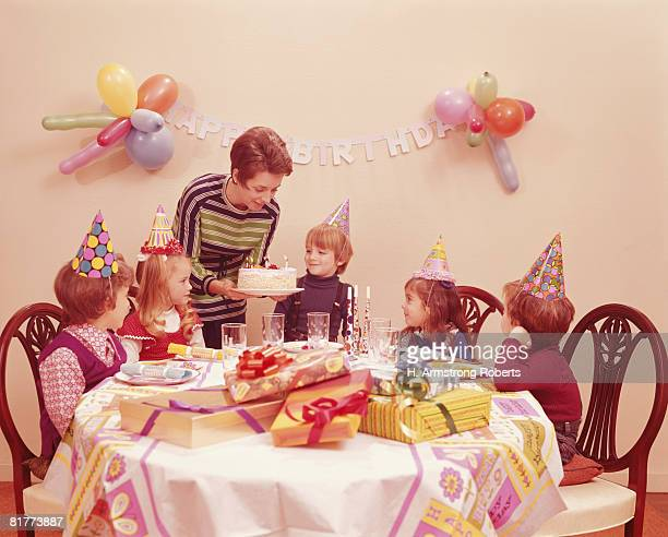 Five children at birthday party, mother serving birthday cake. (Photo by H. Armstrong Roberts/Retrofile/Getty Images)