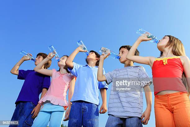Five children drinking water from bottles.