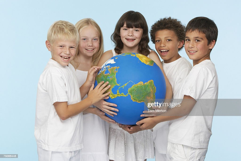 Five children holding a globe indoors : Stock Photo