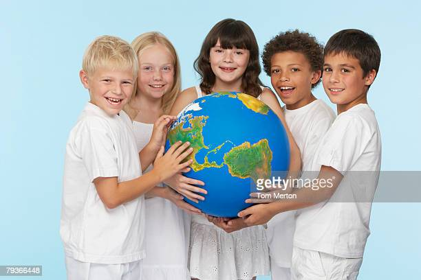 five children holding a globe indoors - world kindness day stock photos and pictures