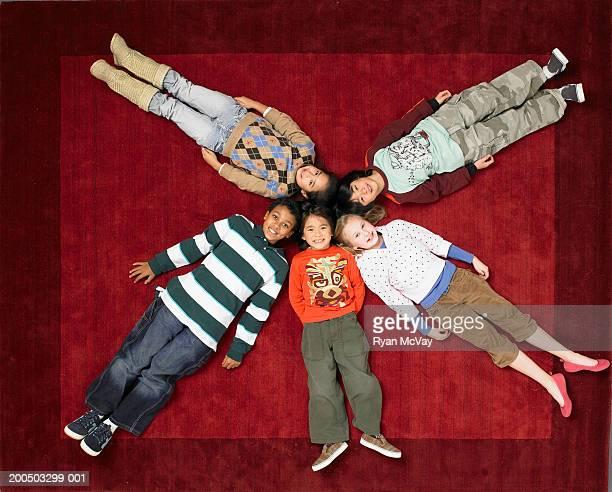 Five children (6-10) lying in circle on floor, overhead view
