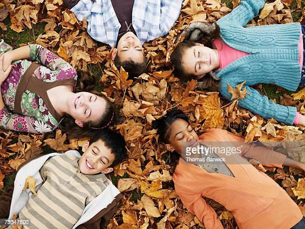 Five children (9-11) lying on leafy floor in woodland