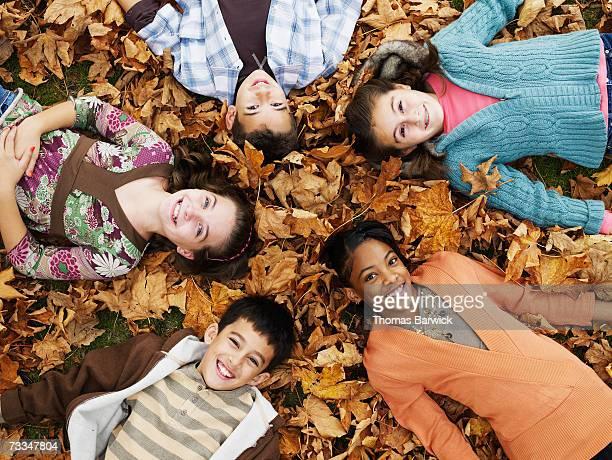 Five children (9-11) lying on leafy floor in woodland, portrait