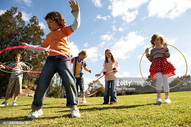 five children (7-12) playing with plastic hoops in park - children only stock pictures, royalty-free photos & images