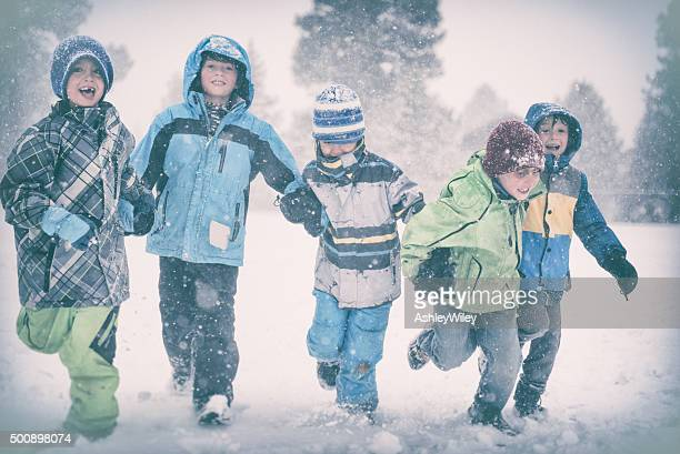 Five children run and play in a snowy storm