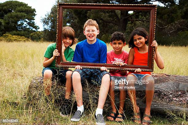 Five children sitting down holding a picture frame