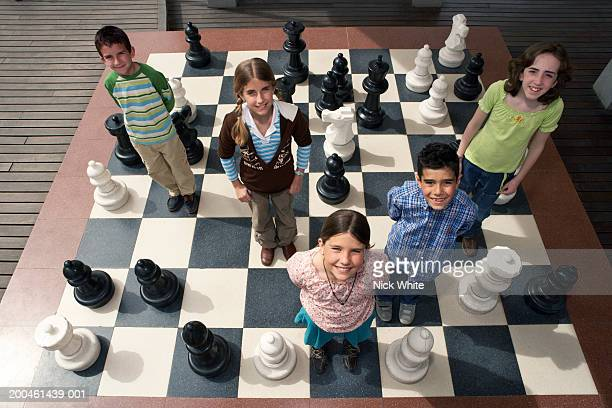 Five children (8-11) standing on giant chess board, smiling, portrait