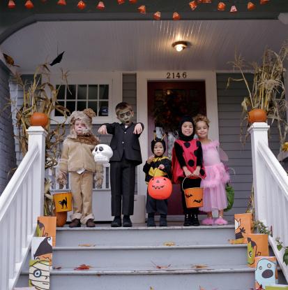 Five children standing on porch, wearing Halloween costumes, portrait - gettyimageskorea
