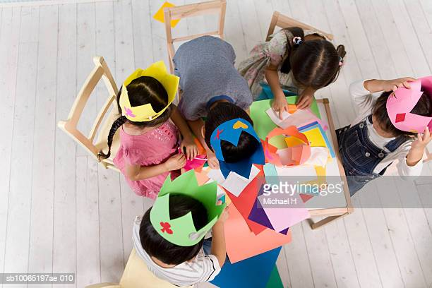 Five children (2-5) wearing paper crowns sitting at table with origami, high angle view