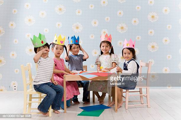 Five children (2-5) wearing paper crowns sitting at table with origami