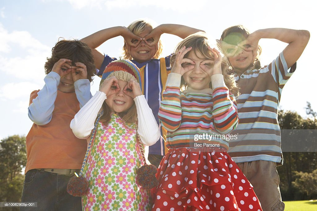 Five children (7-12) with fingers over eyes, portrait (lens flare) : Stock-Foto