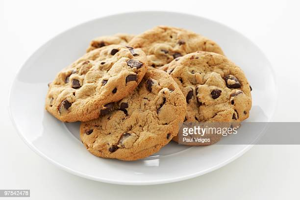 Five Chocolate Chip Cookies on a White Plate