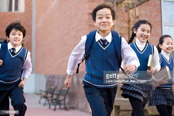 Five classmates running through campus
