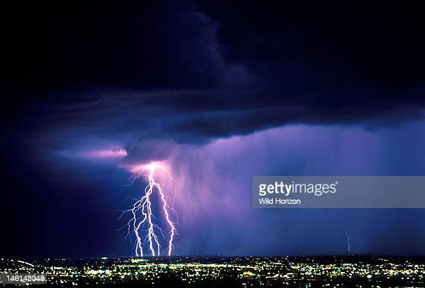 Five cloudtoground lightning strikes on leading edge of rain curtain sweeping over city at night Tucson Arizona USA