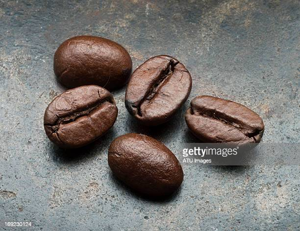five coffee beans on steel