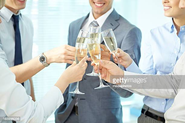Five colleagues clinking champagne filled glasses